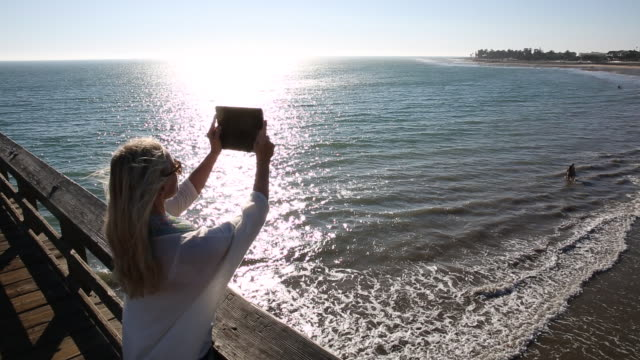 pan of woman walking on pier and takes photo with digital tablet, overhead view - ventura stock videos and b-roll footage