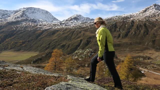pan of woman walking to rock ridge crest, looks out - 若い女性だけ点の映像素材/bロール