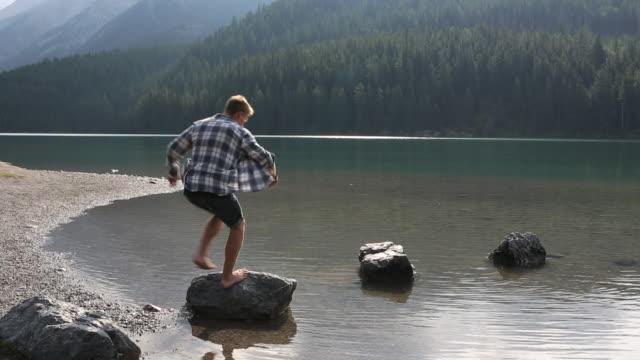Pan of young man jumping across stepping stones at lake