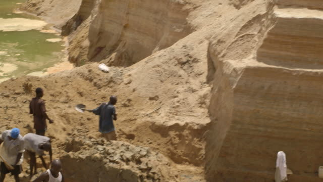 pan onto workers digging in a diamond mine pit in sierra leone. - sierra leone stock videos & royalty-free footage