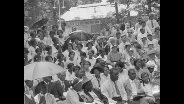 pan outdoor audience of predominantly africanamerican people some with umbrellas and some fanning themselves as they listen to secretary of commerce... - 1927 bildbanksvideor och videomaterial från bakom kulisserna