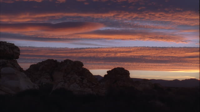vidéos et rushes de pan over a mountainous landscape and grassy field at sunset/sunrise in the karoo - karoo
