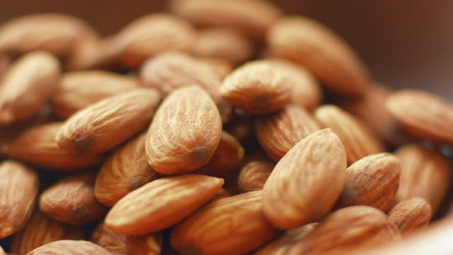 pan over bowl filed with whole almonds - almond stock videos and b-roll footage