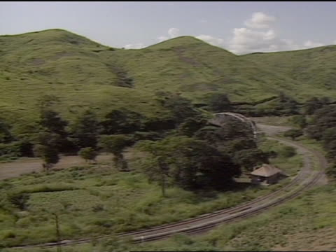 1989 ha pan over congo mountain valley with river running along base of mountain and dirt roadway running through grassland populated w/ trees and... - strohdach stock-videos und b-roll-filmmaterial