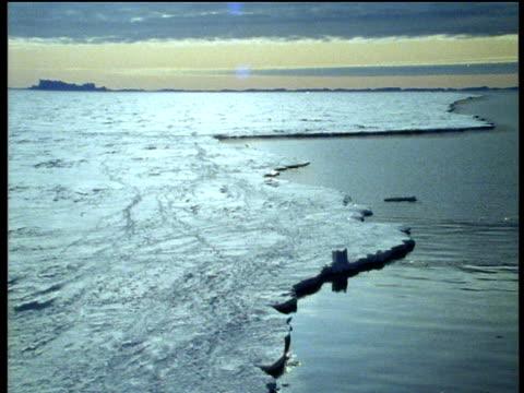 Pan over edge of sea ice in Antarctica, sun reflecting in water