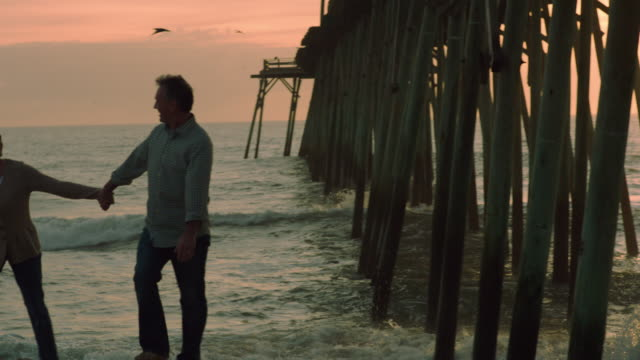 pan over from dock to couple walking up from sunset shore holding hands (slo-mo) - wilmington north carolina stock-videos und b-roll-filmmaterial