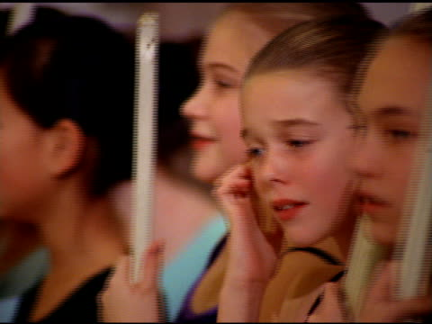 pan over girls standing around in ballet class holding wooden sticks, seattle - gymnastikanzug stock-videos und b-roll-filmmaterial