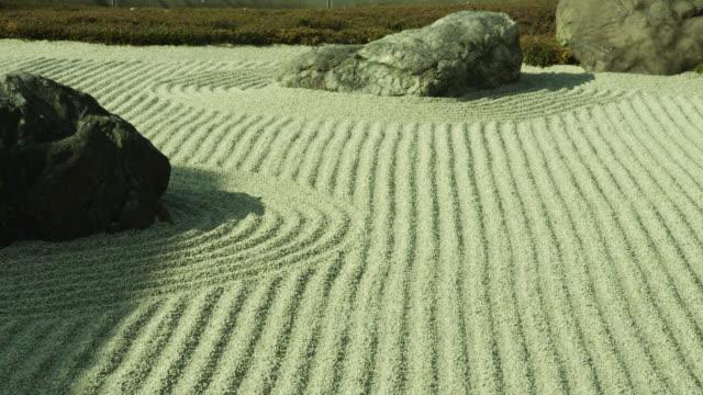 pan over lines of raked gravel in zen garden at gyokudo art museum. - zen stock-videos und b-roll-filmmaterial