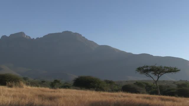 Pan over scrubland and mountainous ridge.