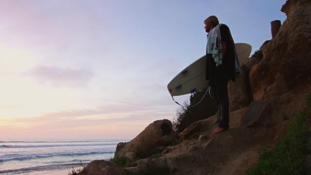 Pan Over Surfer on Cliffside Footpath