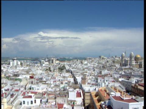Pan over town of Cadiz with white buildings and red roofs sea in distance.