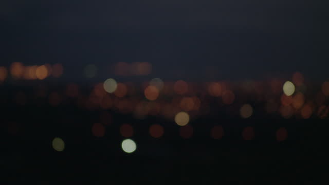vidéos et rushes de pan over twinkling bokeh of a town - sans mise au point