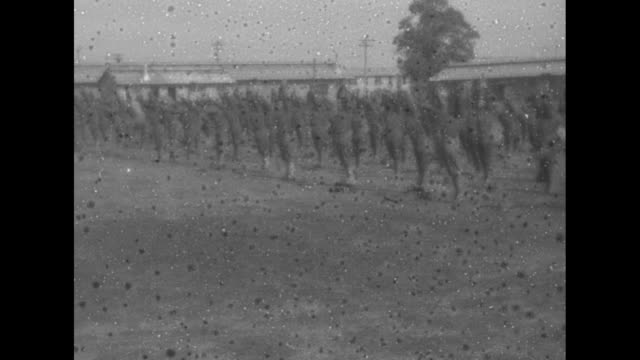 vídeos de stock, filmes e b-roll de pan parade ground and barracks of camp custer, with military band marching in foreground / parade of recruits through the camp / recruits do... - oficial posto militar