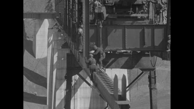WS pan partial bridge across river in bottom of canyon large gap at far end of bridge / workers on rail car on bridge help lift large girder / VS...