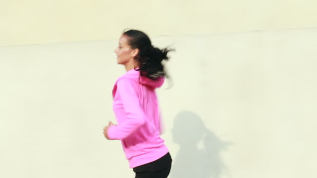 MS Pan profile shot of young woman jogging with shadow on wall at sunset