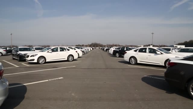 Pan R L of parked Hyundai vehicles Parked Hyundai vehicles at delivery center Close view of Hyundai badge in front of Hyundai vehicles parked at...