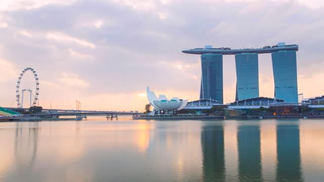 pan r marina bay and singapore skyline at dawn - marina bay sands stock videos and b-roll footage