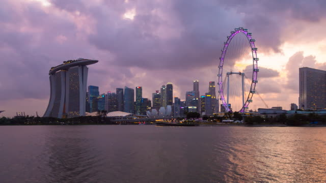 pan r marina bay and singapore skyline at sunset - marina bay sands stock videos and b-roll footage