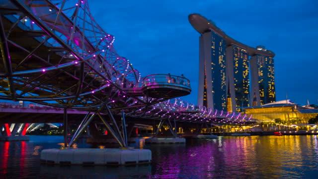 pan r marina bay and singapore skyline with helix bridge at night - marina bay singapore stock videos and b-roll footage