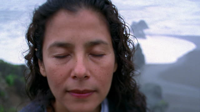 Pan rack focus from high angle waves crashing on beach to close up face of Hispanic woman with eyes closed / California