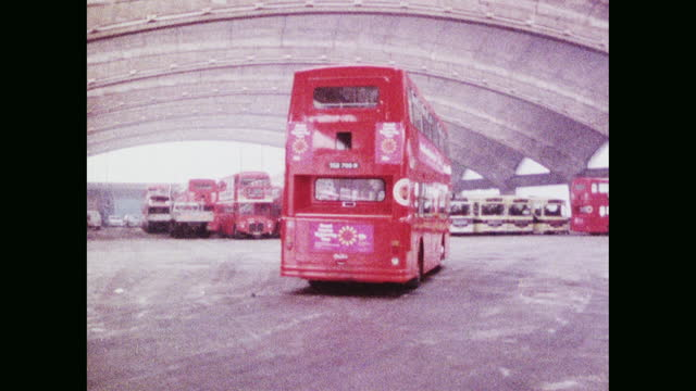 pan red london bus enters stockwell bus garage; 1973 - moving past stock videos & royalty-free footage