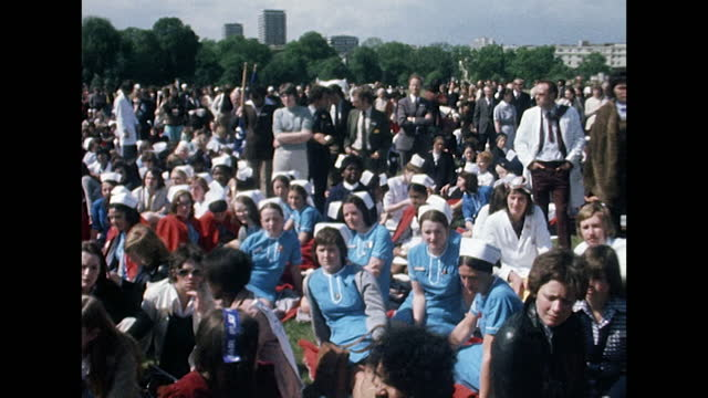 pan right across a large crowd of nurses and doctors assembled in hyde park during a peaceful protest rally over fair pay; 1974. - headwear stock videos & royalty-free footage