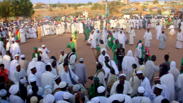 Pan right across a Muslim religious gathering in a public square in Khartoum.