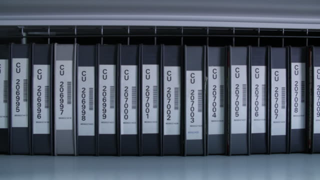 stockvideo's en b-roll-footage met pan right across a row of numbered digibeta tapes on a shelf - bbc archives