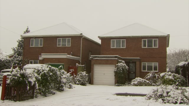 ms pan right across a row of snow covered suburban houses, united kingdom - snow stock videos & royalty-free footage