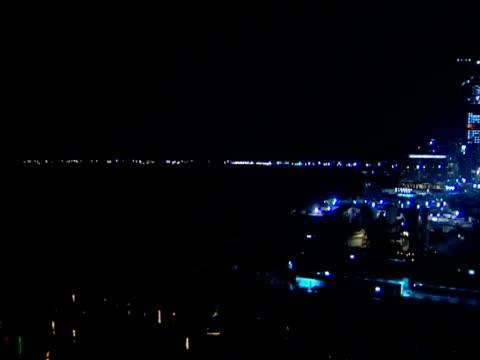Pan right across brightly illuminated construction site at night Dubai