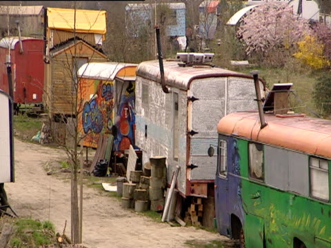 pan right across colourful new age commune of caravans and alternative housing east berlin - new age stock videos and b-roll footage