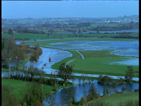 pan right across countryside village and the burst banks of a sussex river to partially flooded fields - sussex stock videos & royalty-free footage