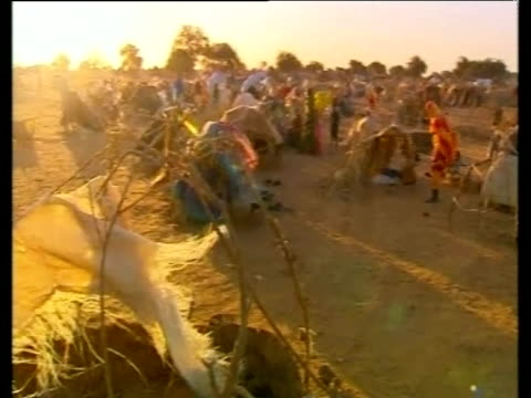 Pan right across crowded refugee camp as wind blows through tents Kalma Sudan Nov 05