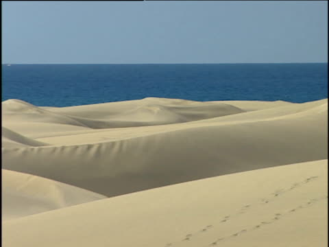 pan right across dunes of maspalomas sea and blue sky fill background; playa del ingles - grand canary stock videos & royalty-free footage