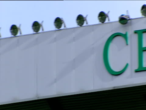 pan right across glasgow celtic football club sign on north stand bordered by bank of floodlights and inscription bears inception of club in 1888... - 彫刻画点の映像素材/bロール