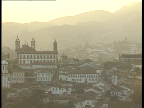 pan right across hillside colonial town with mountain backdrop at sunset ouro preto brazil - spira tornspira bildbanksvideor och videomaterial från bakom kulisserna