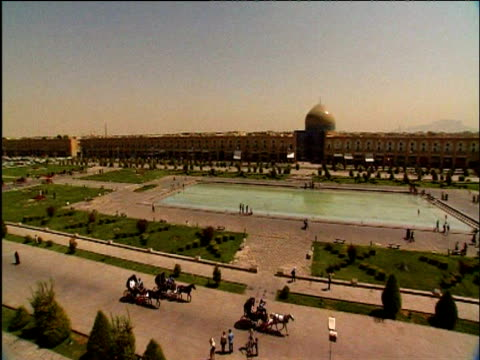 Pan right across Imam Square with reservoir in centre and Imam mosque in background Isfahan