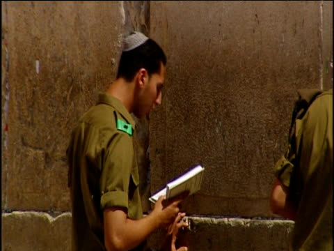 pan right across israeli soldiers preying at wailing wall jerusalem - gerusalemme est video stock e b–roll