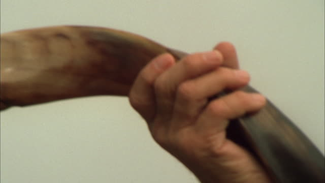 Pan right across Jewish man blowing on shofar, South Africa Available in HD.