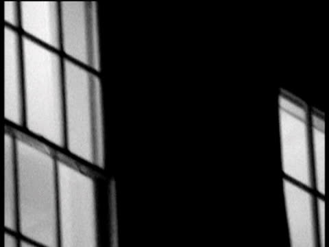 pan right across lit up windows at night black and white filter effect applied - fensterrahmen stock-videos und b-roll-filmmaterial