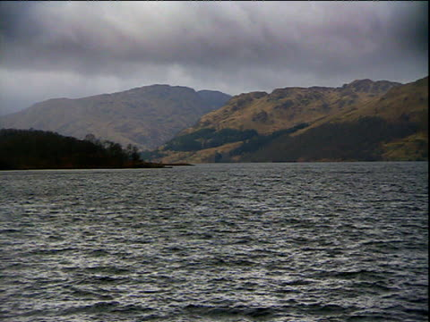 vídeos de stock, filmes e b-roll de pan right across loch and hills scotland - loch