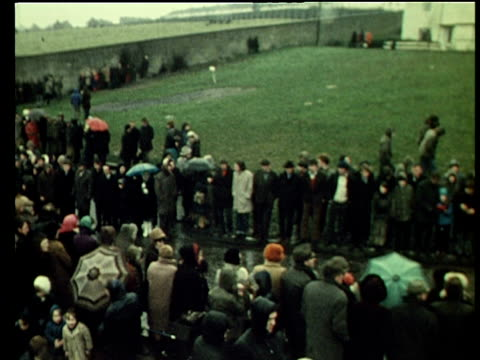 pan right across mourners lining road leading to st mary's church where funerals of bloody sunday victims are being held creggan estate londonderry;... - domenica video stock e b–roll
