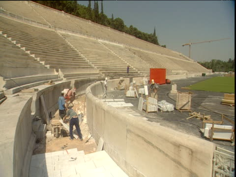 pan right across panathinaikon stadium during renovation process for the 2004 olympic games athens - erezione video stock e b–roll