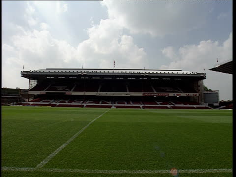 Pan right across pitch to red seats in football stand Highbury football stadium London