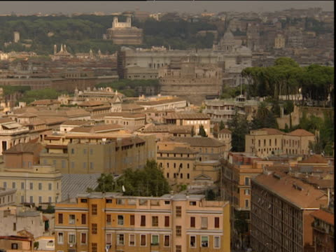 pan right across rome skyline showing apartment block and houses - roma città video stock e b–roll