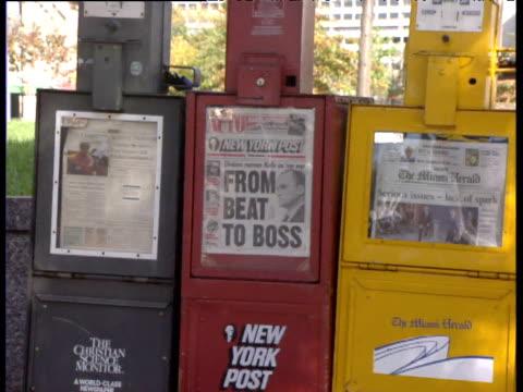 Pan right across row of newspaper dispensers Washington D.C