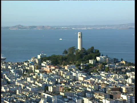 pan right across san francisco bay including coit tower on telegraph hill and sprawling metropolis of local residences boats sail on calm sea in background - coit tower stock videos & royalty-free footage