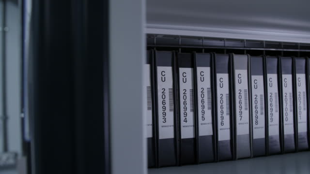 Pan right across shelving containing a row of Digibeta tapes in a row