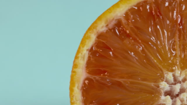 pan right across the cross-section of an orange against a plain blue background. - still life stock videos and b-roll footage