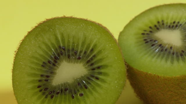 pan right across, then pan left across, a halved kiwi fruit against a plain, bright background. - ascorbic acid stock videos & royalty-free footage
